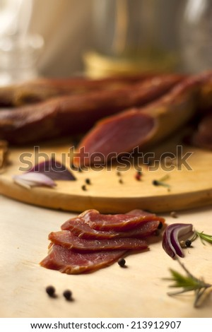 Home-made smoked loin, sirloin prepared by polish butcher. Fresh slices of loin. Presented on wooden desk-board with onion and pepper grains.  - stock photo