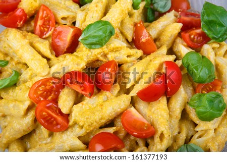 Home made tomato pasta on plate with fresh basil leaves on wooden background - stock photo