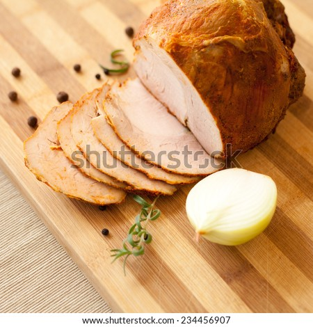 Home-made whole boiled chicken ham prapered by polish butcher. Presented on a wooden desk-board. Part of ham is cut to slices. Nobody. Organic food. - stock photo