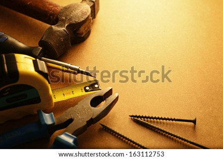Home maintenance tool kit in a sepia toned image arranged in a semi circle on the border with a hammer, pliers, screwdriver, tape measure and nails surrounding copyspace - stock photo