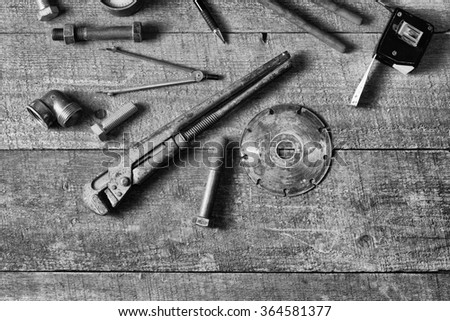 Home master concept. Tape-measure, internal screws, bolts, manometer, diamond wheel, on old wood table. Top view. Copy space.  - stock photo