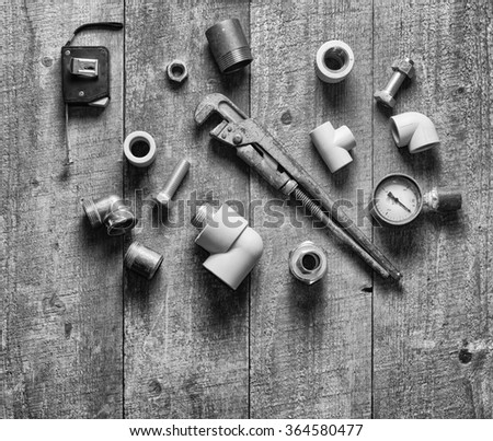Home master concept. Tape-measure, internal screws, pipe screw, PVC pipe connectors, manometer on old wood table. Top view. Copy space. - stock photo