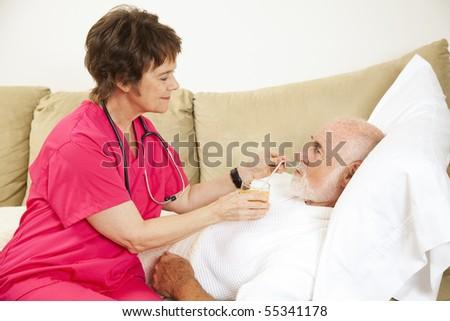 Home nurse helps elderly patient drink a glass of orange juice. - stock photo