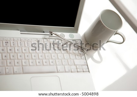 Home office area by the window - laptop screen intentionally blacked out. - stock photo
