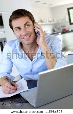 Home office worker talking on mobile phone - stock photo