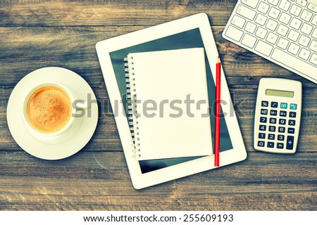 Home office working station. Workplace with digital tablet pc, keyboard and cup of coffee on wooden table. Retro style toned picture - stock photo