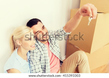 home, people and real estate concept - happy couple with key and cardboard boxes moving to new place - stock photo