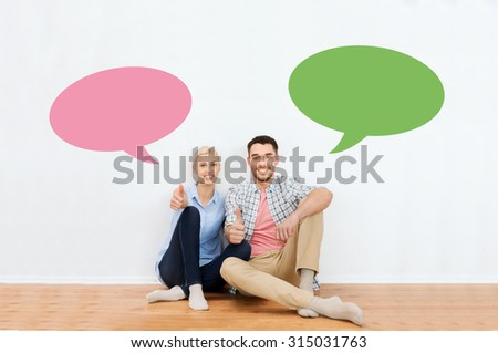 home, people, repair, moving and real estate concept - happy couple sitting on floor and showing thumbs up at new place with empty blank text bubbles - stock photo