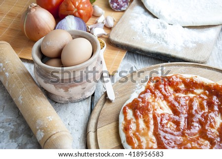 Home pizza original set, pizza dough and ingredients on wooden table. Colorful pizza with mozzarella cheese, chicken, sweet pepper and parsley. Italian cuisine home cooking., soft focus. - stock photo