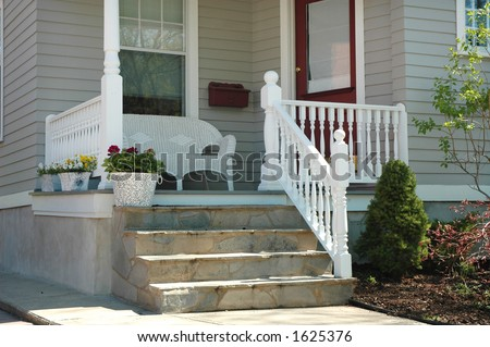 Home porch with white wicker seat, front door entrance, steps, planter with flowers - stock photo
