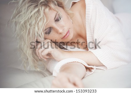 Home portrait of beautiful young woman resting in bed - stock photo