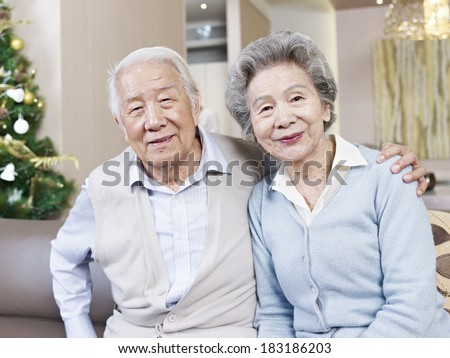 home portrait of senior asian couple smiling - stock photo