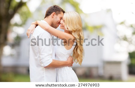 home, real estate, people, love and dating concept - happy couple hugging over summer house background - stock photo