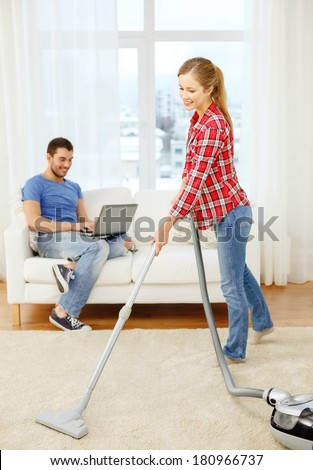 home, relations and cleaning concept - smiling woman with hoover and young man with laptop at home - stock photo