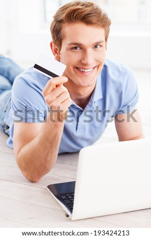 Home shopping. Handsome young man working on laptop and holding credit card while lying on the floor at his apartment - stock photo