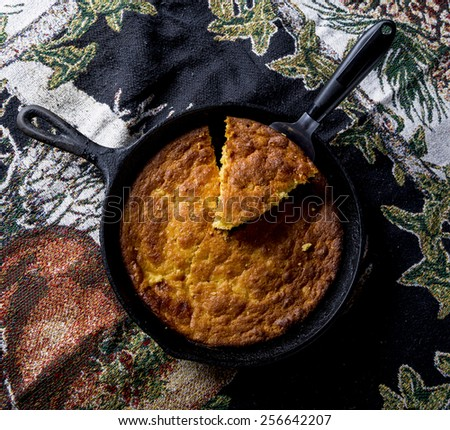Home Style corn bread being served from a cast-iron skillet. - stock photo