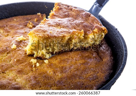 Home Style corn bread being served from a cast-iron skillet isolated on 