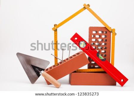 home symbol , bricks and mason tools isolated on white - stock photo