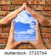 Home symbol made from hands over a brick with a window into blue sky conceptual photo illustration - stock photo
