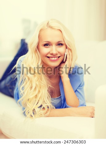 home, technology and communication concept - smiling woman with smartphone lying on couch at home - stock photo
