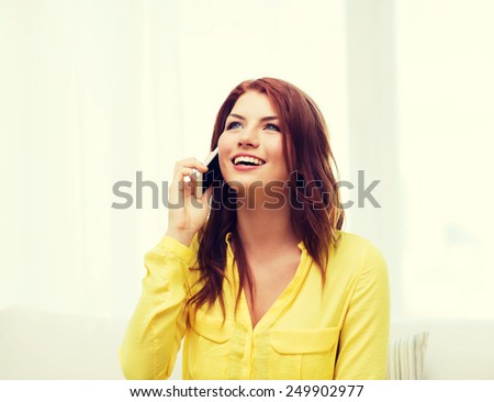 home, technology and communication concept - smiling woman with smartphone sitting on couch at home - stock photo