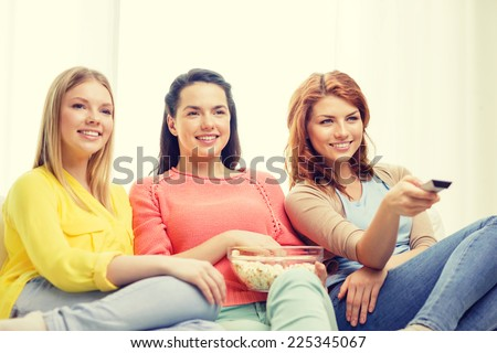 home, technology and friendship concept - three smiling teenage girl watching tv at home and eating popcorn - stock photo