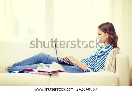 home, technology and internet concept - busy teenage girl lying on the couch with laptop computer at home - stock photo