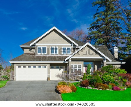 Home with covered entry and double three car garage with the dark blue sky in the autumn time of the year. Vancouver. - stock photo