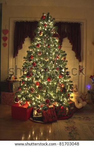 Home with lighted Christmas tree, presents,fireplace,stockings - stock photo