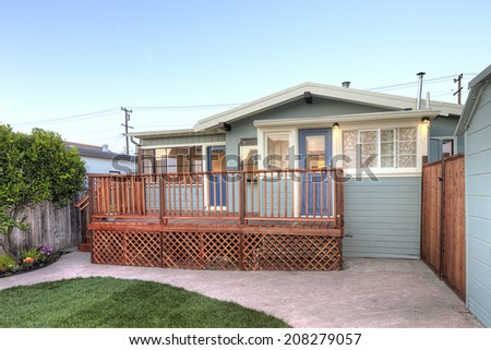 Home with wooden deck and green lawn  - stock photo