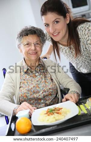 Homecarer preparing lunch for elderly woman  - stock photo
