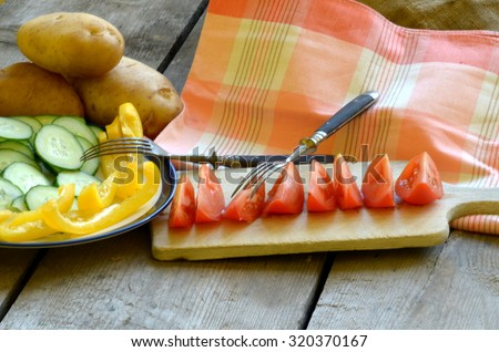 Homegrown cut tomato, pepper and cucumber and potatoes on rustic table - stock photo