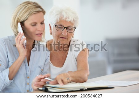 Homehelp booking medical appointment for elderly woman - stock photo