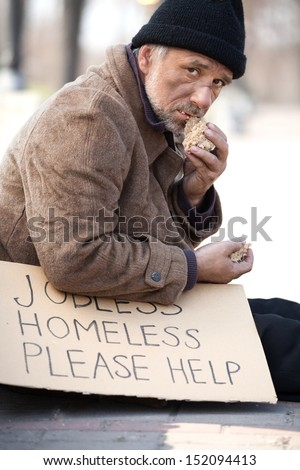 Homeless and hungry. Close up of depressed senior man eating bread - stock photo
