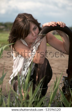Homeless girl  drinks water from a natural source - stock photo