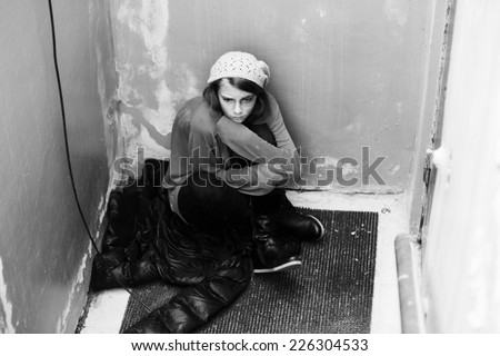 Homeless girl sitting on the floor - stock photo