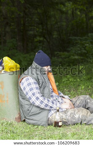 Homeless leaning against the garbage bins - stock photo
