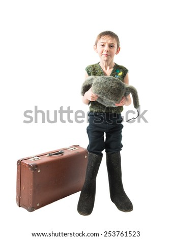 Homeless little boy standing in felt boots next to a suitcase and begs for alms holding in hands hat on a white background - stock photo