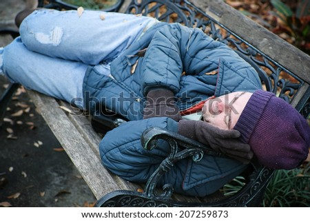 Homeless man asleep on a park bench with a bottle of wine.   - stock photo