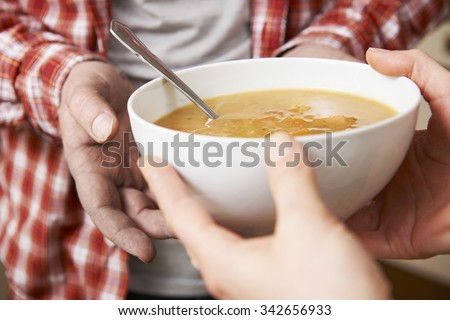 Homeless Man Being Handed Bowl Of Soup By Volunteer - stock photo