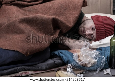 Homeless man lies on cardboard covered with a blanket - stock photo