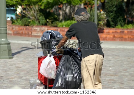 Homeless man pushing cart - stock photo