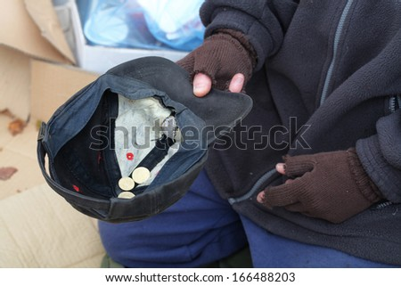 Homeless man's hand with cap for a coins - stock photo