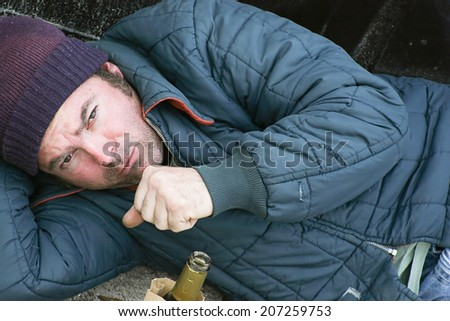 Homeless man sleeping on the ground in the cold with a cough.   - stock photo