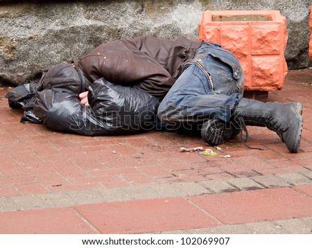 Homeless man sleeps on a pavement - stock photo