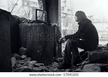 Homeless man watching broken TV-set in the ruined interior. Shallow depth of field due to the tilt lens for movie effect - stock photo