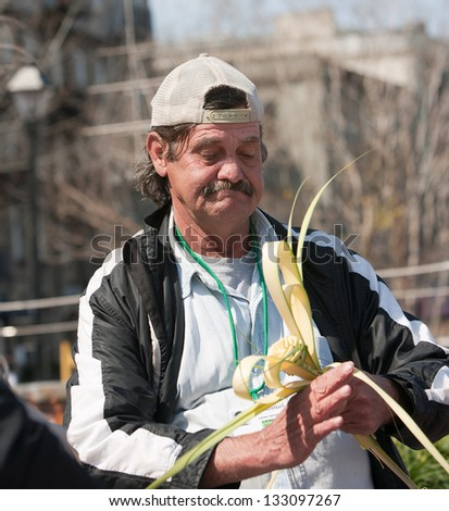 Homeless man working and making a rose out of a piece of palm. - stock photo