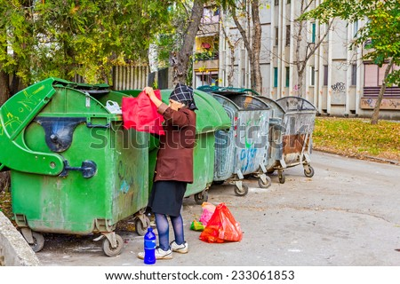 Homeless woman is searching for food in garbage dumpster/Woman in poverty/Woman is searching something in container - stock photo