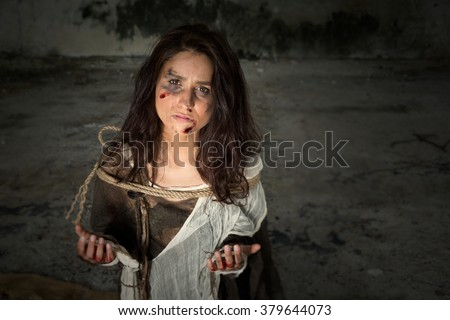 Homeless young woman dressed in rags in a derelict building - stock photo