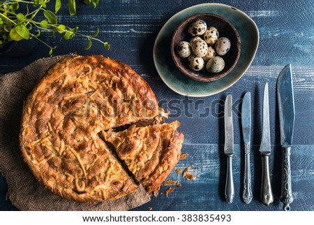 Homemade and baked double cheese pie on blue wooden background with quail eggs,Easter concept  - stock photo